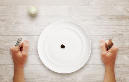 Diet concept of breakfast. Olive in an empty plate with hands on table.